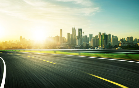 freeway at sunset, motion blur with city background . Banco de Imagens