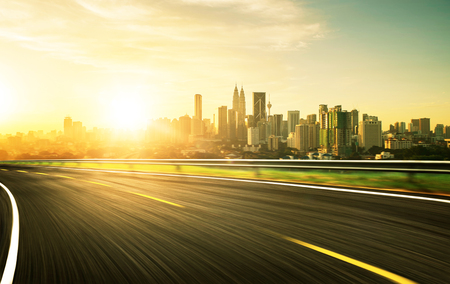 urban road: freeway at sunset, motion blur with city background . Stock Photo