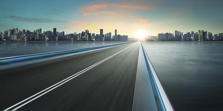 Het viaduct van de motion blur met de skyline van de stad achtergrond. koude stemming. panorama. Stockfoto