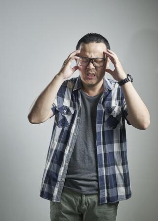 splitting headache: front view of man having splitting headache, on grey background