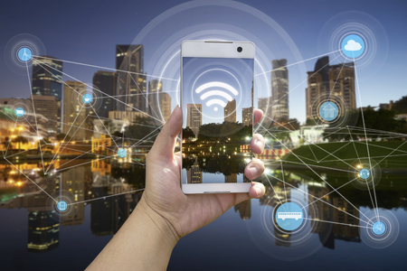 都市景観と wifi ネットワーク接続概念と白い携帯電話を持つ手