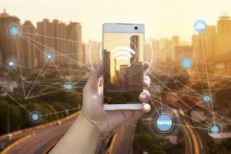 손을 도시 풍경과 interenet 네트워크 연결 개념 흰색 전화를 들고 스톡 콘텐츠