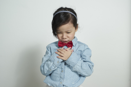 pout: little girl portrait pout sad isolated studio on grey background Stock Photo