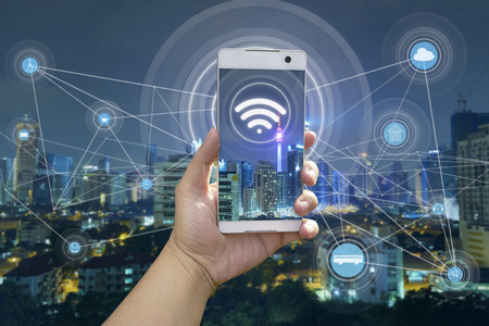 손을 도시 풍경과 와이파이 네트워크 연결 개념 흰색 전화를 들고