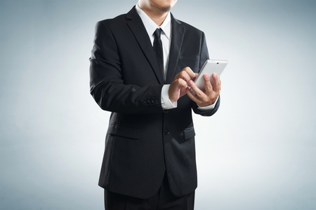 clipping  messaging: Corporate male executive messaging via phone , with clipping path Stock Photo