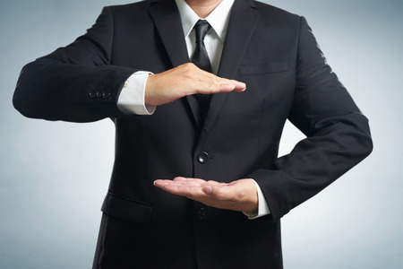 Businessman in suit with two hands in position to protect something (focus on hand, blur out the suit). It indicates many aspects such as car insurance coverage, support, assurance, reliability. Archivio Fotografico