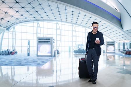 스마트 폰에 남자 - 공항에서 젊은 비즈니스 사람. 사무실 건물 또는 공항 내 행복 미소 캐주얼 도시 전문 사업가 사용하여 스마트 폰입니다.