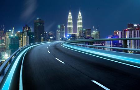 Highway viaduc flou de mouvement avec la ville de fond. scène de nuit.