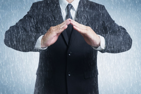 household accident: Businessman in suit with two hands in position to protect in rainy weather day (focus on hand, blur out the suit). It indicates many aspects such as car insurance coverage, support, assurance, reliability.
