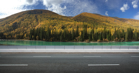 noon: Empty asphalt road and lake mountain background .