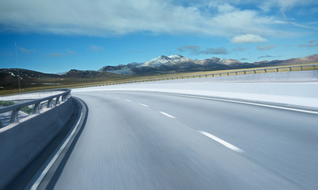 noon: Highway overpass motion blur with mountain background . Stock Photo