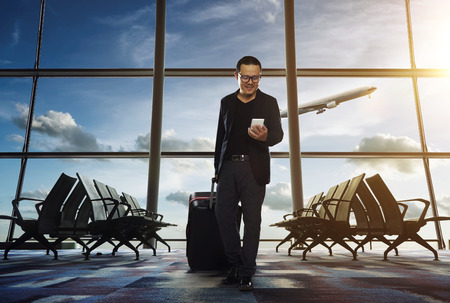 Man on smart phone - young business man in airport. Casual urban professional businessman using smartphone smiling happy inside office building or airport.