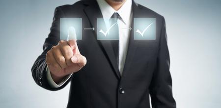 Business process workflow illustrating management approval, flowchart with businessman in background Standard-Bild