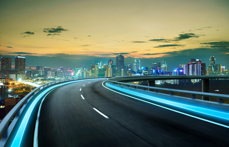 Blue neon light highway overpass motion blur with city  skyline background , night scene . Stock Photo