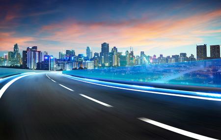 블루 네온 빛 고속도로 육교 운동은 도시의 스카이 라인 배경, 밤 장면 흐림.