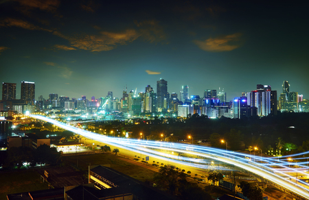 Abstract and car lighttrail  background, city skyline downtown background and highway interchanged nigh view . Stock Photo