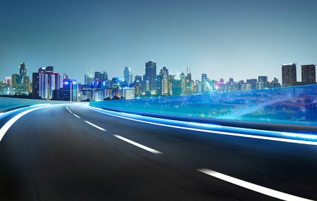 Blue neon light highway overpass motion blur with city  skyline background , night scene . Stock Photo