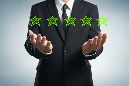 five star: Businessman holding five star rating.