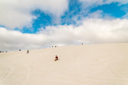 land slide: LANCELIN, AUSTRALIA - NOVEMBER 6, 2016: People sand surfing the Lancelin Sand Dunes . Families enjoying sand surfing recreation in Lancelin, Western Australia.
