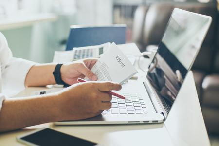 ビジネスの男性は、彼のデスク、ノート パソコン、電卓、コーヒー、選ぶフォーカスのカップに彼の履歴書を確認します。 写真素材