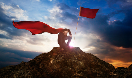 Businessman in a suit and cape hero on top of a mountain,Business Success concept. Stockfoto