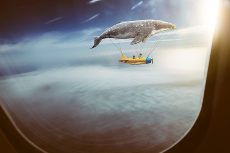 Whale floats in the air above the clouds carrying children in a yellow airplane,seen through window of an aircraft , dreams and travel concept .