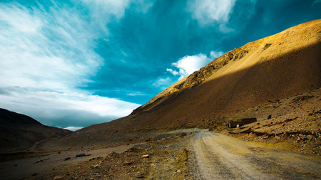 Stunningly beautiful mountain road through the Western Tibet with blue and white clouds sky .
