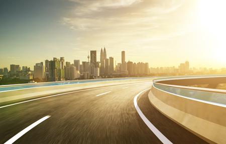 Highway overpass modern city skyline background . Evening scene . Foto de archivo