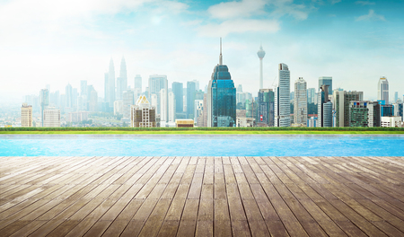 Empty wooden deck with swimming pool , Beautiful pool side view with  city skyline . Stock Photo