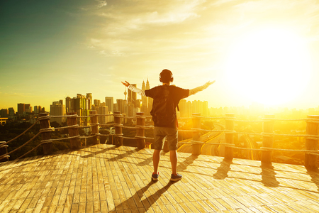 Silhouette man raise hands up for him success, beautiful cityscapes skyline view. morning sunrise scene .