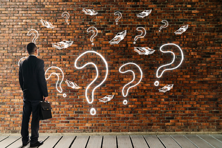 technology symbols metaphors: Businessman looking and thinking about investment opportunities front of a brick wall with the question marks and money icon . Business metaphor of equity investments concept .