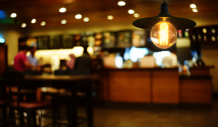 Hanging retro light lamp decor glowing in out of focus restaurant interior background . Stock Photo