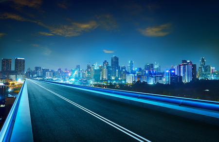 Empty asphalt flyover with city skyline ,night scene . Stock Photo