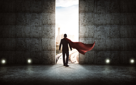 accomplishments: Businessman in a suit and cape stand on stair against concrete wall with huge door ,sunrise scene city skyline outdoor view . Stock Photo