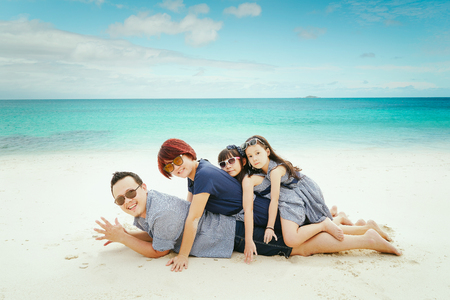 Portrait of happy asian family at sandy beach in summer vacation .