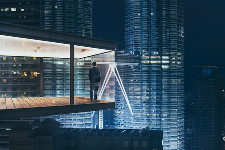 Businessman in an modern sky office by night with beautiful city skyline view .