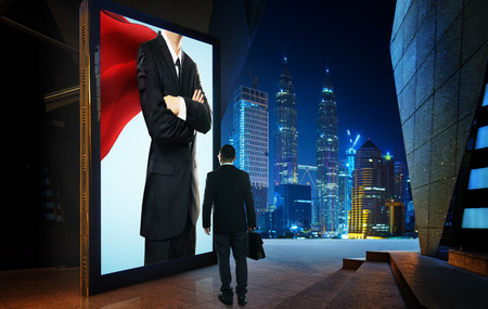 successfulness: Young businessman looking the hero businessman on the advertising billboard screen . Successful businessman concept .