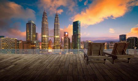 Wooden balcony terrace with wooden relax chair , kuala lumpur city skyline background , night scene . Stock Photo