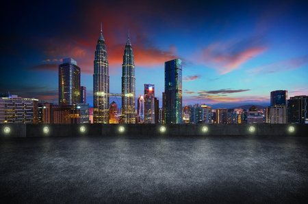 Empty side view asphalt car park with kuala lumpur city skyline , night scene .