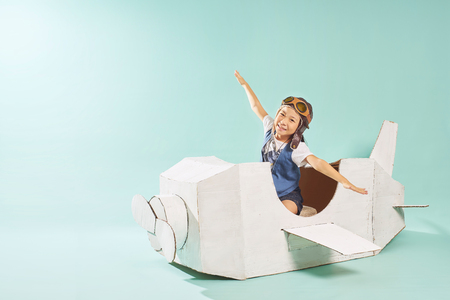 Little cute girl playing with a cardboard airplane. White retro style cardboard airplane on mint green background . Childhood dream imagination concept . Stock Photo