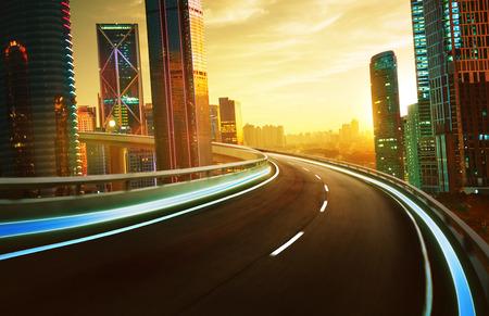 Snelweg viaduct bewegingsonscherpte met skyline van de stad en stedelijke wolkenkrabbers, zonsondergang en twilight scène. Stockfoto