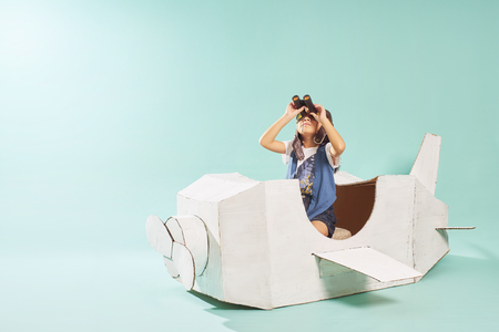 Little cute girl playing with a cardboard airplane. White retro style cardboard airplane on mint green background . Childhood dream imagination concept . Archivio Fotografico