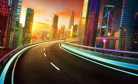 Highway overpass motion blur with city skyline and urban skyscrapers , golden hour scene.