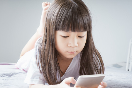 Little asian  girl using smartphone and lying on the bed . child addicted phone. Foto de archivo