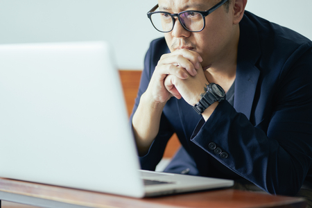 Close Up view of serious businessman looking on screen of laptop .