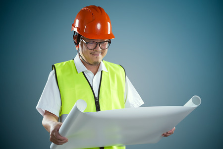 Portrait of professional construction contractor worker with hard hat and holding construction blue print plan with light blue background . Stock Photo