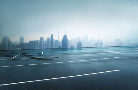Vacie la carretera de asfalto mojada con el fondo de niebla del horizonte de la ciudad, lloviendo día.