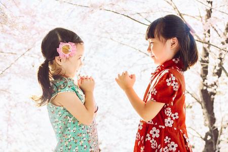 Two adorable girl wearing cheongsam during chinese new year season .
