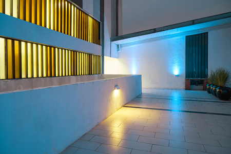 Modern exterior design courtyard with blue and yellow spotlight , night scene .