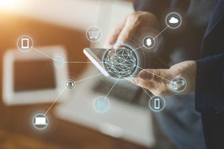 Mann, der das intelligente Telefon bildet, das on-line-Einkaufen und Bankverkehr bildet. Der Hintergrund jedoch unscharf.